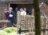 Peter Capaldi with crew members on the Doctor Who set with large wooden horse far right of image