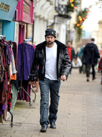 A bearded Nicolas Cage wearing plaid jacket and beanie hat, walking alone in Glastonbury, Somerset.