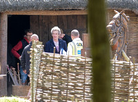 Peter Capaldi and crew members on the Doctor Who set. Also in shot a basket filled with swords, and a large wooden horse,