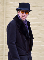 Nicolass Cage waist up wearing top hat and orange sunglasses