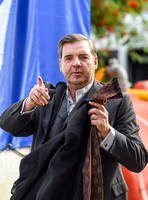 Brendan Coyle carrying a jacket and tie in left hand and gesticulating with his right.