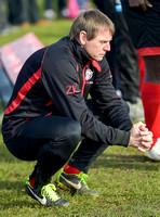 Stuart 'Psycho' Pearce for Longford AFC wearing team tracksuit, crouched down, hands clasped together, contemolation.