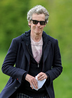 Close up of Peter Capaldi as Doctor Who wearing a long dark jacket, checked trousers and Ray Ban sunglasses