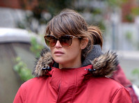 Gemma Arterton close up wearing red padded coat with fur trim and oversized sunglasses