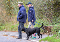 Side shot walking right to left of Zara Phillips in blue MUSTO jacket, polo cap and beige jodhpur with boxer and labrador, and unknown older male.