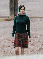 Rachel Weisz on beach wearing 60's style headscarf, green turtle neck sweater and red plaid 'A' line skirt and blue short wellington boots