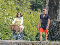 Emilia Clarke riding bicycle wearing lemon floral dress, lemon jumper and turquoise neckerchief alongside Matthew Lewis in orange and black running gear