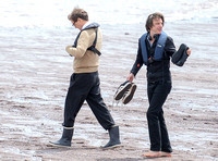 Colin Firth walking into the sea, wearing beige cardigan talking to director James Marsh