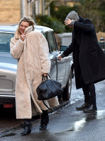 Kate Moss in calf length faux fur coat giggling with Jefferson Hack in background.
